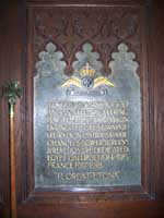 Carved panelling and a memorial plaque to the north of the font