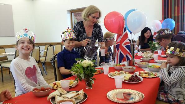 Children with crowns eating, with adults assisting