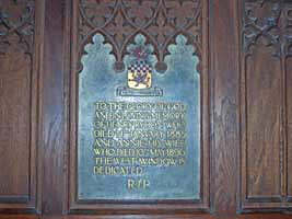 Carved panelling and a memorial plaque south of the font